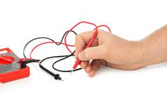 Hand and electric multimeter - stock photo