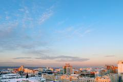 Panoramic views of city on background beautiful blue sky on winter day - stock photo