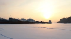 Old big freight ships on frozen river at winter snowy day Stock Footage