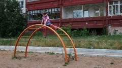 Little girl sits on semicircular ladder and waves hand at playground Stock Footage
