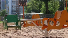 Small colored carousel turns on playground at sunny day Stock Footage