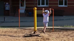 Little girl and boy whirl on whirligig at playground Stock Footage