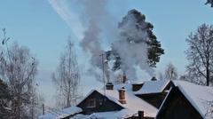 Roof of wooden house with chimneys with white smoke at winter day Stock Footage