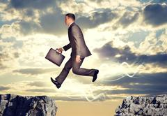 Businessman jumping over abyss Stock Photos