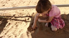 Happy little girl in pink plays with sand on playground at summer Stock Footage