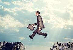 Businessman jumping over precipice - stock photo