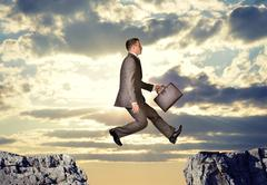 Businessman hopping over abyss - stock photo