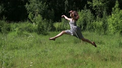 Beautiful girl gracefully jumps on grass at summer day Stock Footage