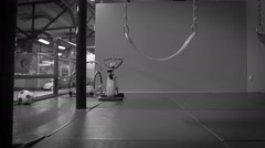 Black and white: recently-left indoor playground with a swing still swaying Stock Footage