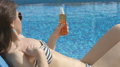 Happy young woman suntanning, applying sunscreen to protect skin - stock footage