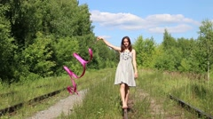 Beautiful girl with ribbon goes on old rail among forest at summer day Stock Footage