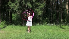 Pretty girl in dress dances with pink ribbon in summer forest - stock footage