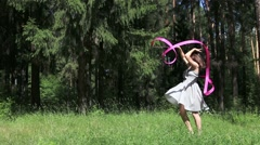 Young woman in dress dances with pink ribbon in summer forest - stock footage