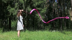 Pretty young woman in grey dress dances with ribbon in summer forest - stock footage