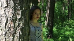 Pretty young woman comes out from behind tree and goes deep into forest Stock Footage