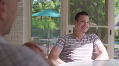 Man in sun room gestures, claps and laughs 4K Stock Footage