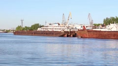 Two small boats float near big cargo barges and passenger ships on river Stock Footage