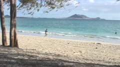 Solo runner on beach, Hawaii Stock Footage