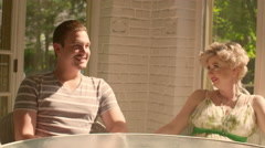 Man and woman talk and laugh in a sunny covered porch 4K - stock footage