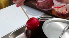 Female hand turns red sweet apple on stick in syrup Stock Footage