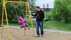 Father swings little pretty girl on swing at playground in cloudy day Stock Footage