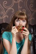 Young beautiful woman drinks coffee from gilt cup on couch in room - stock photo