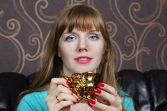 Young beautiful woman smiles and holds gilt cup on couch in room - stock photo