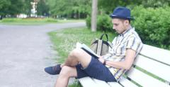 The guy is reading a book in the park. Stock Footage