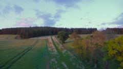 Aerial flight forward over a crop field upto Peniel Heugh, Scottish Borders Stock Footage