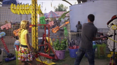 Stock Video Footage of Shot of a man, with a girl, swinging a hammer at a carnival game.