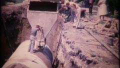 2357 - concrete is poured around sewer pipe to seal it - vintage film home movie - stock footage