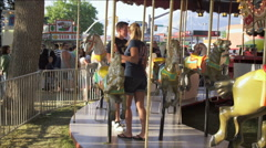 Shot of couple exiting a merry-go-round at a carnival. Stock Footage