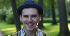 Men's emotions on the background of the park. He looks around and smiles. Stock Footage