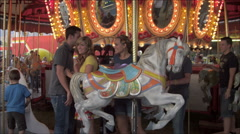 Slow motion shot of couples exiting a merry-go-round. Stock Footage