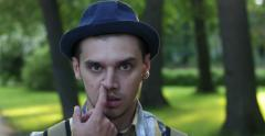 Men's emotions on the background of the park. Picking his nose. Stock Footage