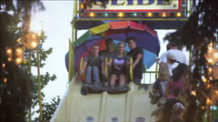 Slow motion shot of boy and girl sliging down a bumpy slide at a carnival. - stock footage