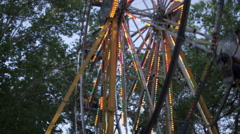 Pan and tilt down a moving ferris wheel Stock Footage