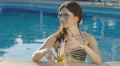 Attractive female drinking cocktail, relaxing in pool. Vacation Footage