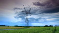 Tracking shot of an electricity tower along a road in the countryside at Stock Footage