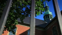 Tracking shot of a church steeple through a fence in Copenhagen, Denmark Stock Footage