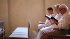 Dolly shot of elderly people reading the bible at a church in Copenhagen, Stock Footage