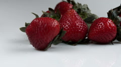 Single strawberry rolling away from the bunch. Stock Footage