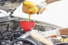 Car mechanic pouring new oil to engine. Stock Photos