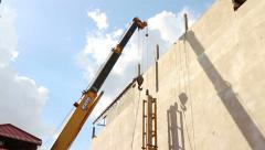 CONSTRUCTION: Crane Lowers Concrete Pile into Piledriver Stock Footage
