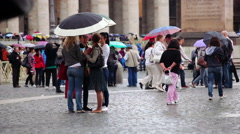 Four young women and tourists in Saint Peter's Square on a rainy day in Vatican Stock Footage