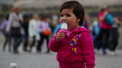 A small girl child licks an ice cream cone in St Peter's Square circa May, 2012 Stock Footage