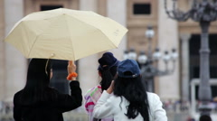 A woman uses an umbrella to shield another woman with a camera in Vatican City. Stock Footage