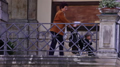 A woman carefully brings a stroller holding a child down some stairs in Rome, Stock Footage