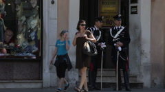 Two uniformed men watch people pass on the street in Rome, Italy. - stock footage