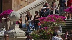 A uniformed man walks down the Spanish Steps, which are crowded with tourists. Stock Footage